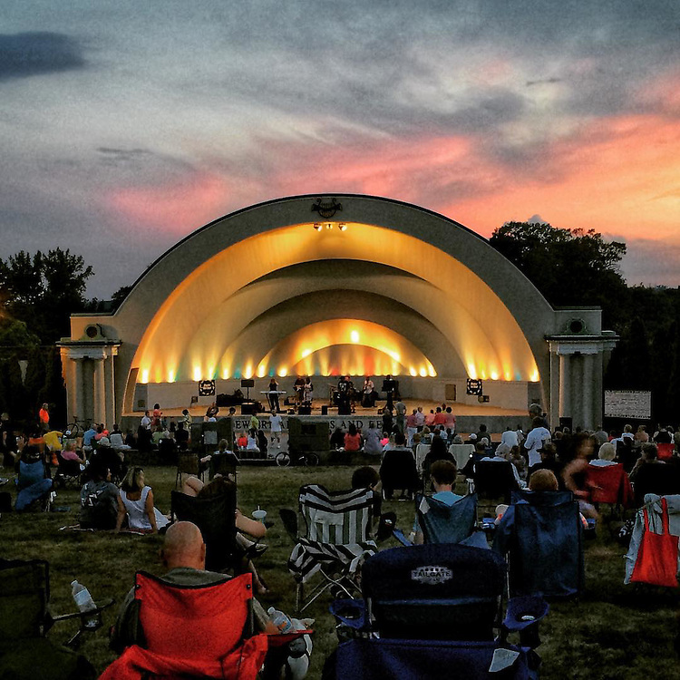 Nekita Waller performs with Shaded Soul in a bandshell for a summer concert as the sun sets.