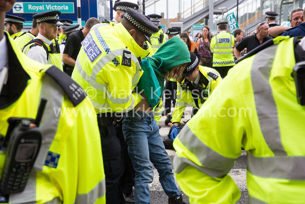 London, UK. 2 September, 2019. Police officers arrest a female activist who had locked on using an arm tube to block a road outside ExCel London on the first day of week-long protests against DSEI 2019, the world's largest arms fair. The first day of creative action was hosted by activists calling for a ban on arms exports to Israel and featured workshops, speakers, street theatre and dance. Israeli arms companies display weapons at DSEI marketed as 'combat-proven' following deployment against Palestinian communities.
