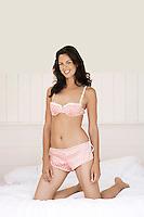Woman in underwear kneeling on bed