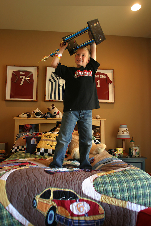 Royal McKee, 7 years-old, stands on his bed while holding one of his racing trophies in his room at his family's home in Las Vegas, NV on Sunday, March 4, 2007.  Royal is professional go kart driver. He has won competitions in Nevada and California.