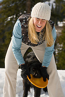 A young woman plays with her dogs in Jackson Hole, Wyoming.