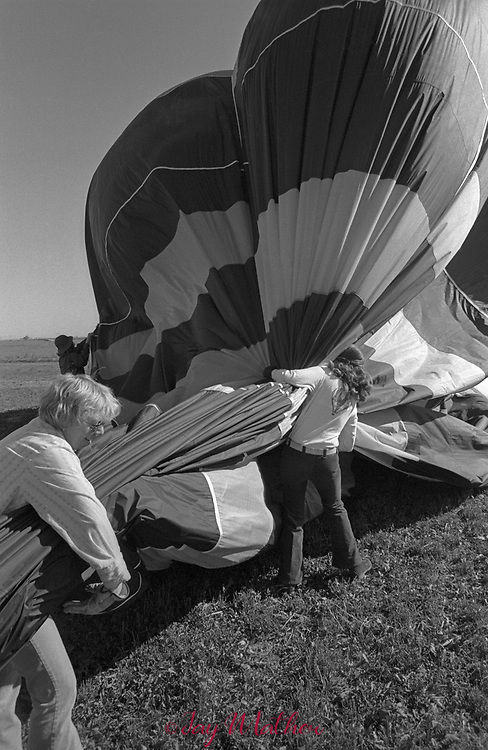 """Sandy (Branham) Kneeland, one of the first female hot air balloon pilots in the United States, takes passengers on a flight near Longmont, Colorado in 1974. One of her balloons was named the """"Grape Escape,"""" for its distinctive purple color. Sandy is one of the founding members of the Colorado Balloon Club. She got her pilot's license in March 1973. She remarried and changed her last name to Kneeland. Notes from Sandy on the flight: Your flight with me was on September 29, 1974 and we launched from Centennial Park in Longmont, and flew to the Southwest but I didn't log miles. It had to be at least 6 to get past the city. We flew in a Cameron Balloon built in Bristol England, and owned by Robert (Bob) Kenny. The name of the balloon was Epanimondas, N62107. I was giving him instruction on that flight. The balloon was black with yellow squares every other gore at 3 levels. My logbook says """" 1st inflation aborted (wind). 2nd one good. Passenger Jay Mather. Fast to SW, worked layers to fly over Discovery [a blue & orange balloon]. 2nd leg: George. 3rd leg: Kenny solo. Very Good. Flight times: 1st leg 1.2 hr, 2-3 leg .8 hr."""