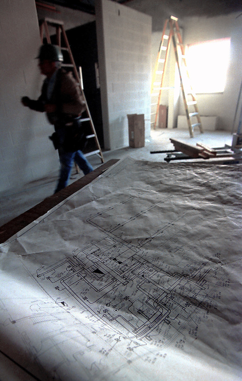 A construction worker walks by plans of a builing under construction.