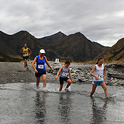 Runners Karen Goodfellow, Carmen Woodhouse and Nigella Woodhouse cross Moke Creek on the Ben Lomond High Country Station during the Pure South Shotover Moonlight Mountain Marathon and trail runs. Moke Lake, Queenstown, New Zealand. 4th February 2012. Photo Tim Clayton
