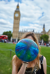 © Licensed to London News Pictures. 01/08/2015. LONDON, UK. Protesters stage a mass inhalation of nitrous oxide from balloons in Parliament Square. The so called legal high, also known as laughing gas, is set to be banned by the proposed Psychoactive Substances Bill.  Photo credit : Cliff Hide/LNP