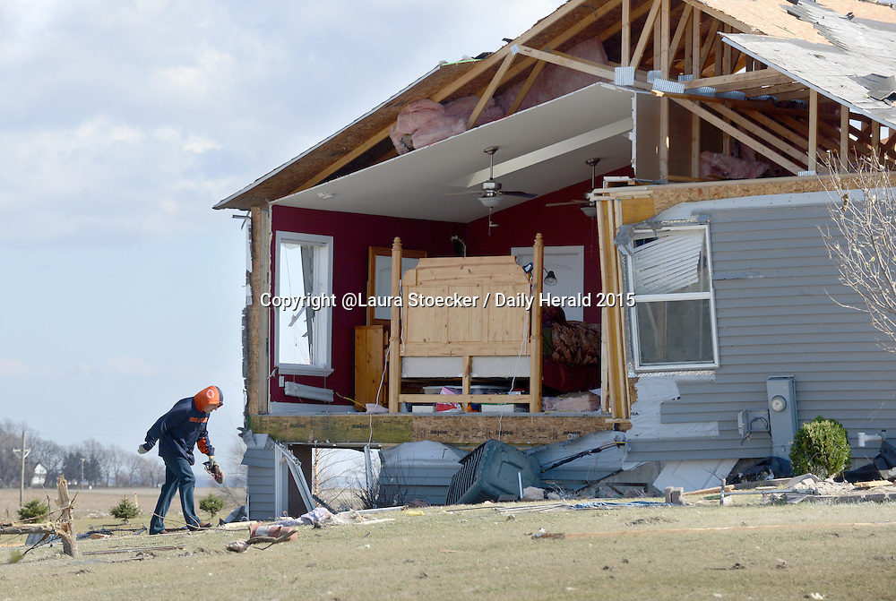 Laura Stoecker/lstoecker@dailyherald.com<br /> A homeowner battles high winds as they walk the grounds around their home on Kuehl Ct. in Rochelle, Illinois Friday.
