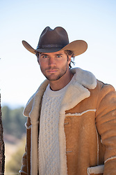 hot young cowboy in a shearling coat outdoors