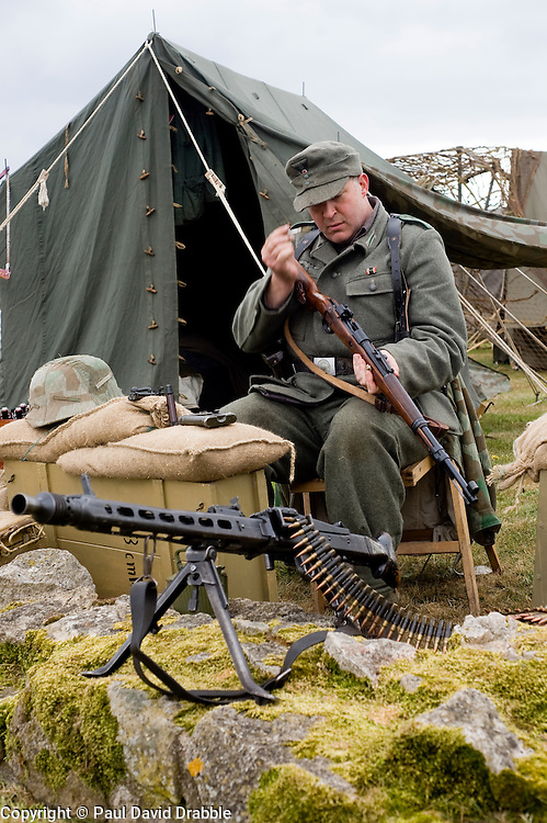 A reenactor from the Northern World War Two Association portraying  life in the field for a German Soldier with the 21st Panzer Division as he sits cleaning a Bolt action Mauser K98 rifle. In the foreground is an MG42 machine gun.<br />