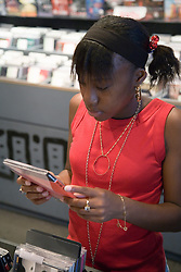Teenaged girl looking through CDs in a music shop,