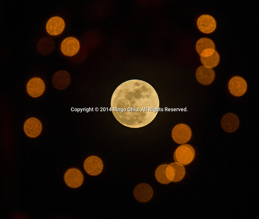 The first full moon (know as Wolf moon) of the year is seen through a holiday wreath at a parking lot on Sunday, January 4, 2015 in Los Angeles, California. (Photo by Ringo Chiu/PHOTOFORMULA.com)