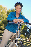 Senior woman leaning on bicycle, portrait