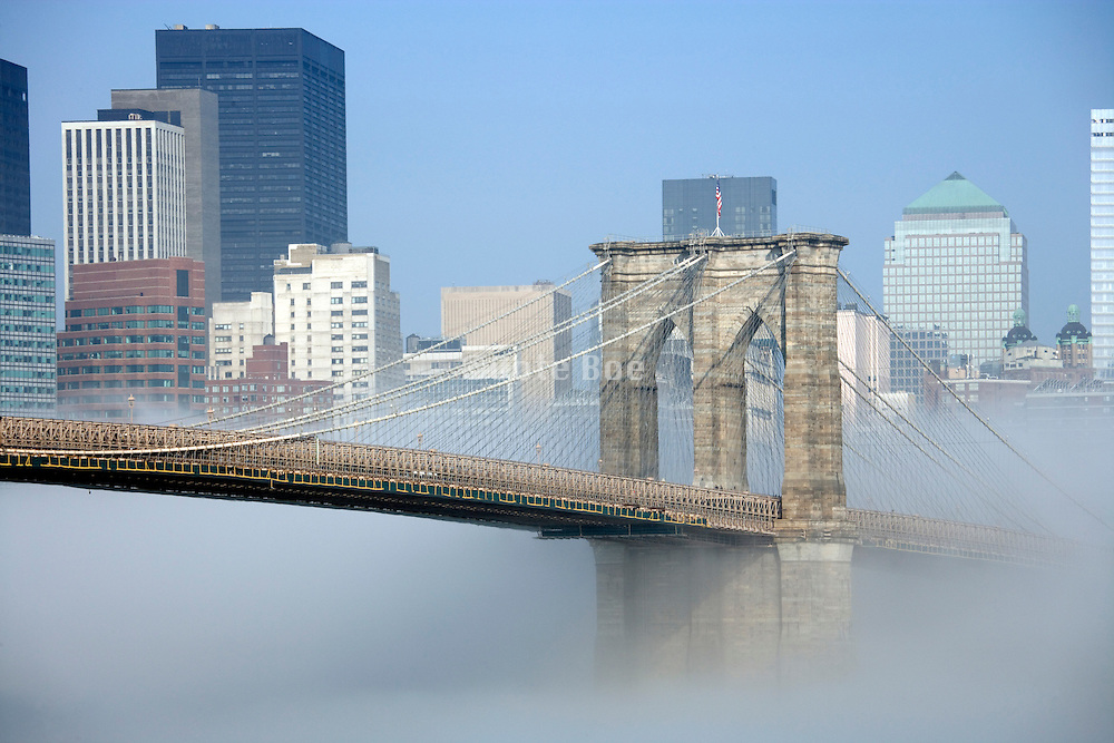 Brooklyn Bridge seen in early morning fog with down town Manhattan in the back ground