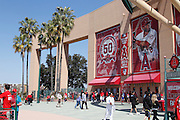ANAHEIM - APRIL 10:  Palm trees blow in the wind as fans cue up to the ticket window below a sign featuring the Los Angeles Angels of Anaheim 50 year anniversary logo and players on the exterior wall of the stadium prior to the game between the Toronto Blue Jays and the Los Angeles Angels of Anaheim at Angel Stadium in Anaheim, California on Sunday April 10, 2011. The Angels won the game 3-1. (Photo by Paul Spinelli/MLB Photos via Getty Images)