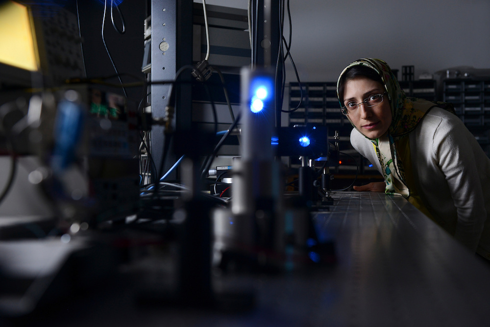 A graduate student in the physics program works in a laser lab in the Science Researh Building.