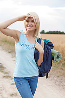 Beautiful young woman with backpack shielding eyes while hiking at field