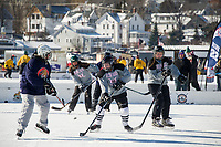 The Bitchin' Babes take on the Quincy Fighting Squirrels during womens division pool play Saturday afternoon at the New England Pond Hockey on Meredith Bay.  (Karen Bobotas/for the Laconia Daily Sun)