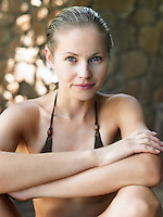 Portrait of young woman in bikini sitting with arms crossed