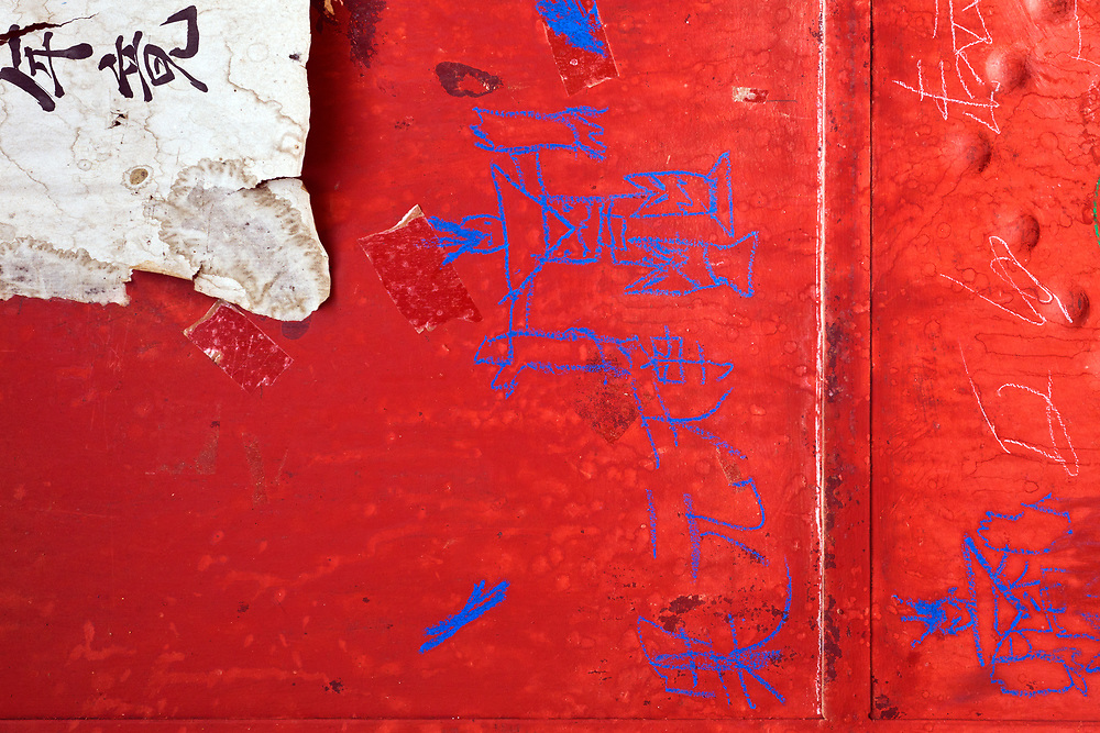 Drawings on a bright red wall in the Mongolian Village of Xin Meng China.