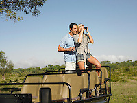 Couple on safari standing in jeep woman looking through binoculars
