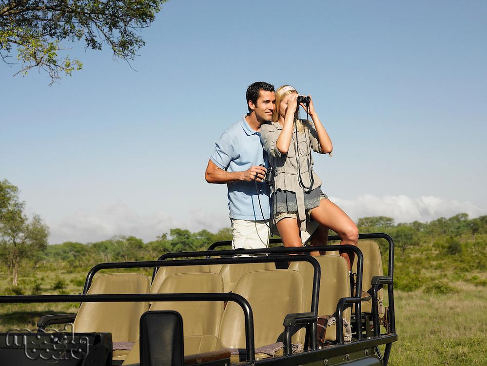 Couple on safari standing in jeep woman looking through binoculars