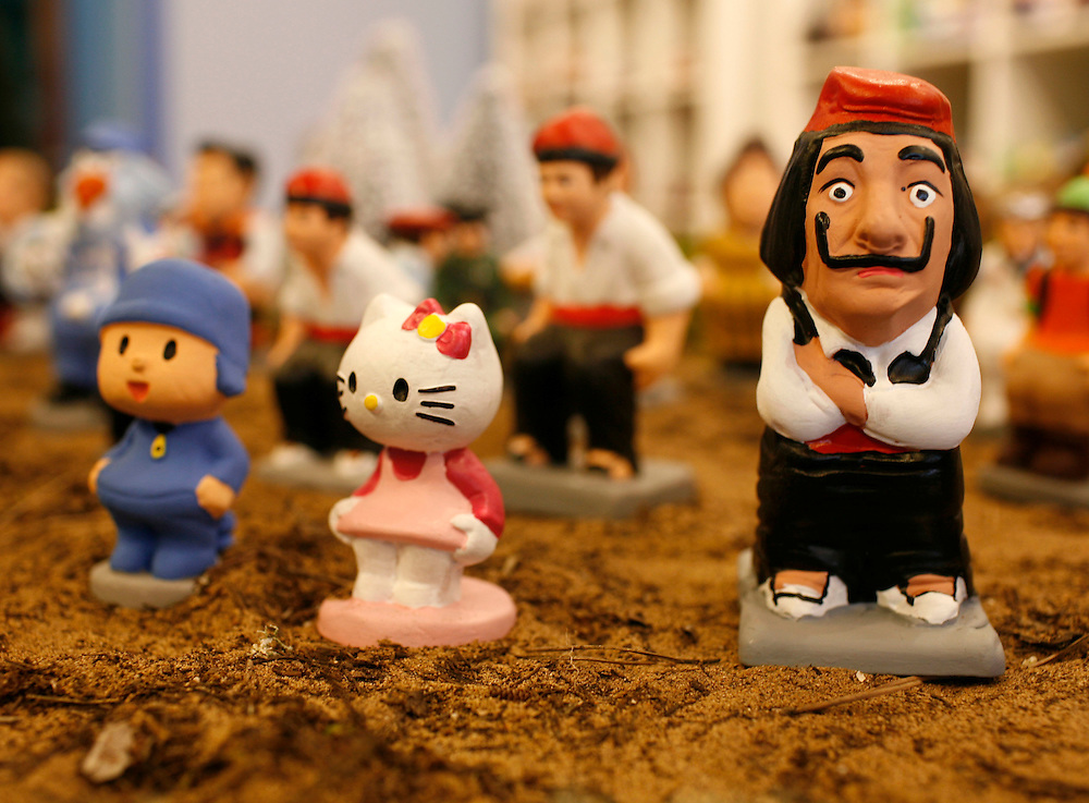"Torroella de Mongri, Spain, 19 November 2009. .A company in Torroella de Montgrí (Girona, Spain) called ""caganer.com"" specialized in the production of ""caganers"" unveiled today  the new figures for Christmas as cartoon Hello Kitty and surrealist painter, Salvador Dali..A ""Caganer"" is a small figure from Catalonia, usually made of fired clay,  and depicted as squating person in the act defecating. .""Caganer"" is Catalan for pooper. It fomrs part of one of the typical figures of  the manger or ""Nativity"" scene together with Mary, .Joseph and the baby Jesus but hidden in a corner. It is a humorous figure, originally portraying a peasant wearing a .barretina (a red stocking hat), and seems to date from the 18th century when it  was believed that the figure's depositions  .would fertilize the earth to bring a properous year. With  the course of the time, the original  personage of this pooping figure .was  substituted with personalities from the political and sports world and other famous personalities."