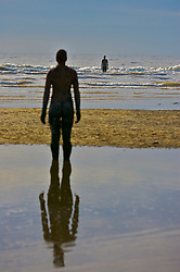 "SEFTON, ENGLAND - SUNDAY, OCTOBER 29th, 2006: One of the 100 Iron-men sculptures that comprise Anthony Gormley's Another Place art installation at Crosby Beach, Sefton. (Pic by David Rawcliffe/Propaganda)..Another place is a spectacular sculpture by Angel of the North artist Antony Gormley. Another Place consists of 100 cast-iron, life-size figures spread out along three kilometres of the foreshore, stretching almost one kilometre out to sea. Each one weighing 650 kilos and is made from casts of the artist's own body. They are shown at different stages of rising out of the sand, all of them looking out to sea, staring at the horizon in silent expectation. According to Antony Gormley, Another Place harnesses the ebb and flow of the tide to explore man's relationship with nature. He explains: ""The seaside is a good place to do this. Here time is tested by tide, architecture by the elements and the prevalence of sky seems to question the earth?s substance. In this work human life is tested against planetary time. This sculpture exposes to light and time the nakedness of a particular and peculiar body. It is no hero, no ideal, just the industrially reproduced body of a middle-aged man trying to remain standing and trying to breathe, facing a horizon busy with ships moving materials and manufactured things around the planet."""