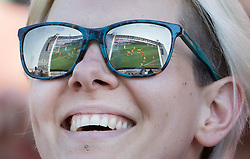 i© Licensed to London News Pictures. 07/07/2018. Brighton, UK.  England's 2-0 quarter-final win over Sweden at the Russian World Cup is reflected in the sun glasses of a football fan on the sea front in Brighton as she watches the game on a giant TV screen. Photo credit: Peter Macdiarmid/LNP