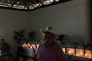 Santos Sánchez, 75, stands in a room at his son Amadeo Martinez Sánchez's home during the wake for 12 La Joya massacre victims, most of these direct relatives of both men. The massacre at La Joya is one of six mass killings that took place in villages within the municipality of Meanguera from Dec. 11-13, 1981, by the US-trained Atlacatl Battalion of the Salvadorian Armed Forces, left over 900 civilian victims and are known collectively as the Massacre at El Mozote and surrounding villages. Earlier in 2016, an amnesty law signed after the 1992 Peace Accords that prevented war crimes from being investigated and tried was lifted by El Salvador's Supreme Court, allowing cases like El Mozote to proceed legally against its perpetrators. La Joya, Meanguera, Morazan, El Salvador. December 11, 2016.