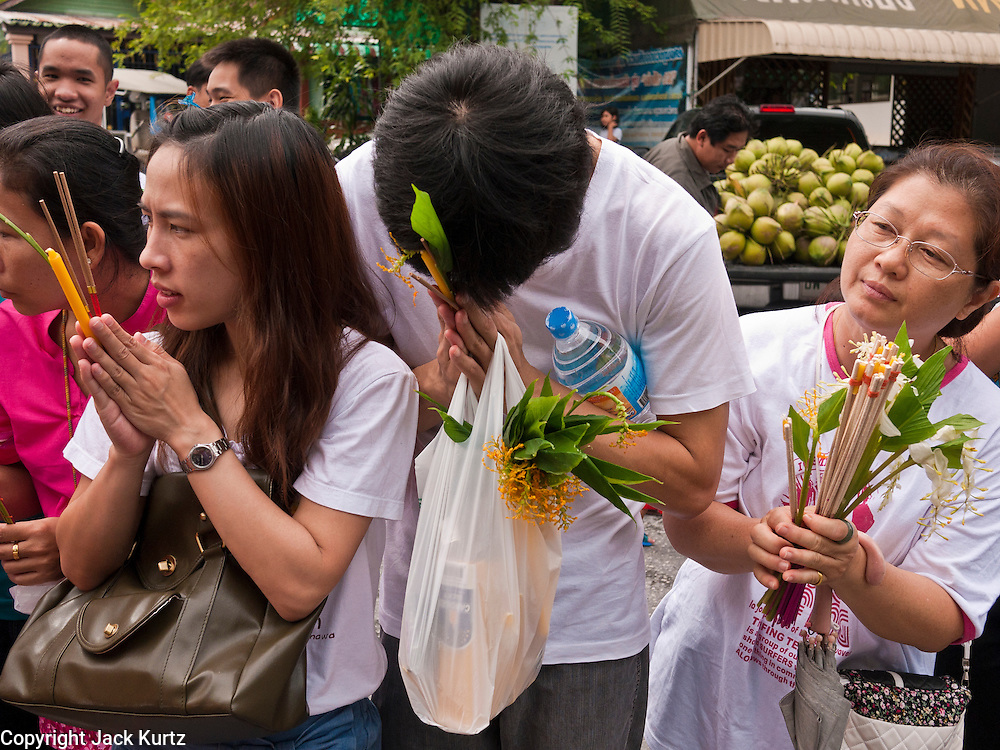 """15 JULY 2011 - PHRA PHUTTHABAT, SARABURI, THAILAND:   People line up to present flowers and candles to the monks during the Tak Bat Dok Mai at Wat Phra Phutthabat in Saraburi province of Thailand, Friday, July 15. Wat Phra Phutthabat is Phra Phutthabat, Saraburi, Thailand, is famous for the way it marks the beginning of Vassa, the three-month annual retreat observed by Theravada monks and nuns. The temple is highly revered in Thailand because it houses a footstep of the Buddha. On the first day of Vassa (or Buddhist Lent) people come to the temple to """"make merit"""" and present the monks there with dancing lady ginger flowers, which only bloom in the weeks leading up Vassa. They also present monks with candles and wash their feet. During Vassa, monks and nuns remain inside monasteries and temple grounds, devoting their time to intensive meditation and study. Laypeople support the monastic sangha by bringing food, candles and other offerings to temples. Laypeople also often observe Vassa by giving up something, such as smoking or eating meat. For this reason, westerners sometimes call Vassa the """"Buddhist Lent."""" The tradition of Vassa began during the life of the Buddha. Most of the time, the first Buddhist monks who followed the Buddha did not stay in one place, but walked from village to village to teach. They begged for their food and often slept outdoors, sheltered only by trees. But during India's summer rainy season living as homeless ascetics became difficult. So, groups of monks would find a place to stay together until the rain stopped, forming a temporary community. Wealthy laypeople sometimes sheltered monks on their estates. Eventually a few of these patrons built permanent houses for monks, which amounted to an early form of monastery.     PHOTO BY JACK KURTZ"""