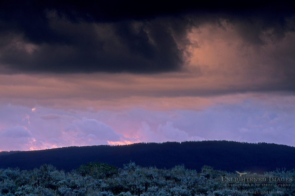Glowing clkouds at sunrise below dark storm clouds ov sagebrush, Grand Teton National Park, Wyoming