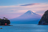Sunrise at Hada Port on the Izu Peninsula, Mt. Fuji towers over the bay. The Torii Gate captures the morning sun. Torii Gate most commonly found at the entrance of a Shinto shrine, where it symbolically marks the transition from the profane to the sacred.