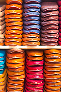 FEZ, MOROCCO - 3rd DECEMBER 2016 - Leather babouche slippers and shoes stacked for sale on shelving in the souks of the old Fez Medina, Middle Atlas Mountains, Morocco.