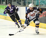 16 Jan 2010: Guildford, England. Paul Dixon (22) of Guildford Flames evades Adam Walker (29) of Manchester Phoenix during the English Premier League match between Guildford Flames  Manchester Phoenix at Guildford (photo by Andrew Tobin/Slik Images)