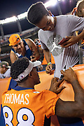 DENVER, CO - AUGUST 11:  Demaryius Thomas #88 of the Denver Broncos signs a tee shirt for a fan during a game against the Minnesota Vikings during week one of the preseason at Broncos Stadium at Mile High on August 11, 2018 in Denver, Colorado.  The Vikings defeated the Broncos 42-28.  (Photo by Wesley Hitt/Getty Images) *** Local Caption *** Demaryius Thomas