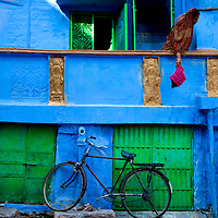 A Bicycle Sits Against Blue Wall as Woman Throws Red Cloth in Jodhpur, Rajasthan, India
