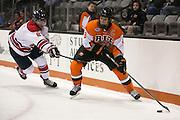 RIT Senior Captain Matt Garbowsky and Brock University's Spencer Turcotte fight for a puck during a game at the Gene Polisseni Center on Saturday, October 4, 2014.