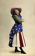 A patriotic young lady in an American flag dress circa 1910. Hand tinted vintage photo. Stars and stripes