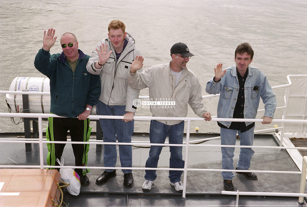 Group of men with learning disabilities standing on ferry waving,