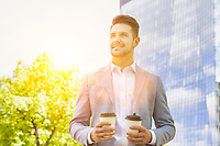 Portrait of young attractive businessman holding two cups of coffee