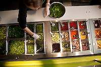 A woman makes a salad behind the counter at Green Bean Salads in St. Louis MO.