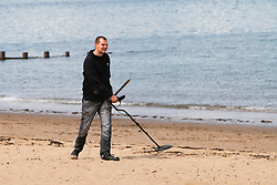 Portobello, Scotland, UK. 9 May 2020. Images from holiday weekend Saturday afternoon during Covid-19 lockdown on promenade at Portobello. Promenade and beach were relatively quiet with a low key police presence. Pictured;  Man with metal detector on the beach. Iain Masterton/Alamy Live News