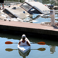 Kayaker Thomas Winters paddled to the X dock at the Santa Cruz Harbor to check out the 1950's era Chris Craft powerboat that sunk in its slip on Wednesday Aguust 20, 2008.
