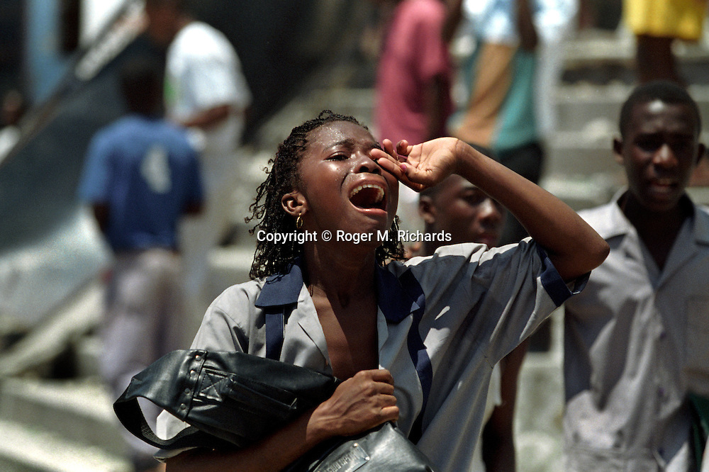 A girl reacts to being teargassed by riot police during violent demonstrations in Port-au-Prince, Haiti, May 1995. (Photo by Roger M. Richards)