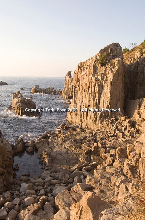 Nov. 26, 2009, Sakai City: This is the rocky cliffs of Tojinbo, a popular tourist attraction on the Japan Sea coast that's also known for the number of suicide deaths that occur here. Located in Sakai City, Fukui Prefecture, this scenic area known for it's coastal beauty, seafood and onsen hot springs resorts now adds suicide as a reason to come here. In 2008 twenty suicides occurred here, but this figure varies between Sakai City officials and a suicide help group dedicated to preventing suicides here. Called Kokoro ni Hibiku Bunshu Henshukyoku, this NPO founded in 2004 by retired policeman Yukio Shige, who along with a group of volunteers patrols the cliffs on a daily basis to deter those contemplating jumping to their deaths. According to Shige, age 65, in the past five years since he founded his NPO, he is responsible for talking 222 people out of killing themselves. But even with Shige's efforts, the deaths here continue and as of late November, 2009, the current number of annual suicides at Tojinbo stands at thirteen. Japan has one of the highest suicide rates in the world and 2009 may surpass the record 34,427 deaths that occurred here in 2003. This increase is though to be a result of the Japanese recession which has been worsened by the global economic downturn. Depression is the number one cause for suicide in Japan, followed by illness and debt. Photo by Torin Boyd.