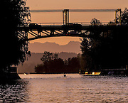 A lone rower passes under the Montlake Bridge. The Cascade Mountains loom in the distance. (Mike Siegel / The Seattle Times)