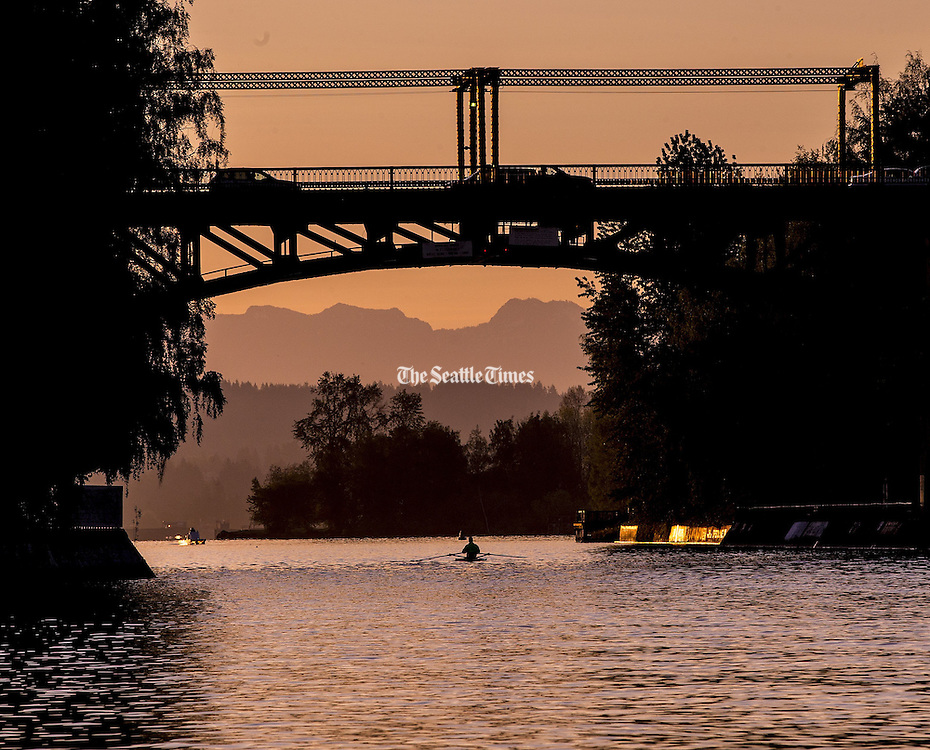 A lone rower passes under the Montlake Bridge early April 19th, 2016. The Cascade Mountains loom in the distance. (Mike Siegel / The Seattle Times)