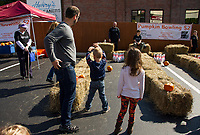 """Families take in """"pumpkin bowling"""" at Bank of NH on Saturday afternoon during Pumpkin Fest.  (Karen Bobotas/for the Laconia Daily Sun)"""