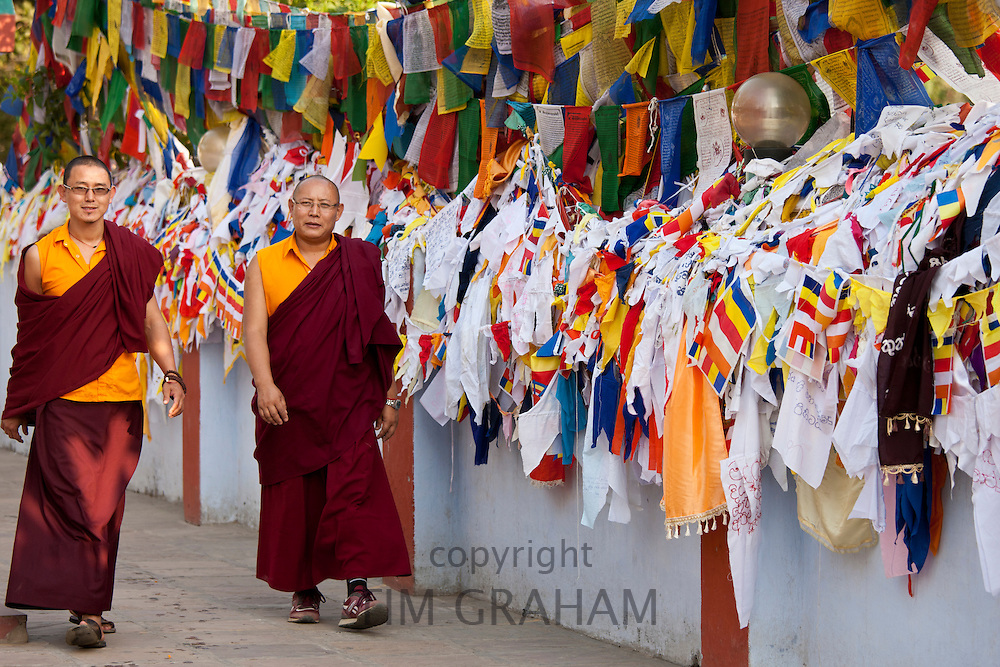 Buddhist monks pass prayer flags at Mulagandhakuti Vihara Temple at Sarnath near Varanasi, Benares, Northern India