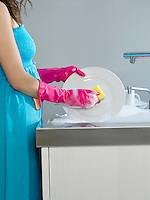 Woman wearing dress and rubber gloves washing dishes side view mid section