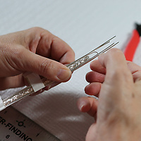Teresa Mendenhall uses small strips of tape to hold the medal in place as she creates a braclet.